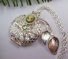 Diese elegante Halskette besteht aus silberfarbenem Metall. Das Medaillon hat einen filigran ausgeschnittenen Deckel, der mit grünem Strass verziert i