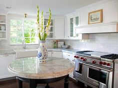 A small, custom round island provides a handy space for prepping meals, without taking up a large footprint in their U-shaped kitchen. A mantel above the stove offers a place to rotate in artwork for display.