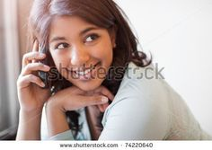 A shot of an asian student talking on the phone in the library by arek_malang, via ShutterStock