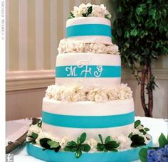 Marne and Grant used the groom's army saber to cut the three-tiered wedding cake. Two tiers were white cake with chocolate fudge filling, and one tier was chocolate cake with raspberry filling. The confection was frosted in white with a band of blue ribbo...
