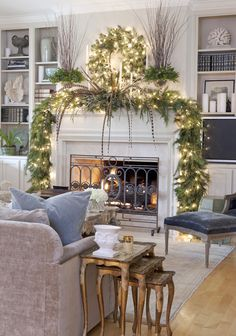 The living room mantle's lush greenery complements the muted Baker sofa and antique rug. Walls are Sherwin-Williams' Softer Tan.
