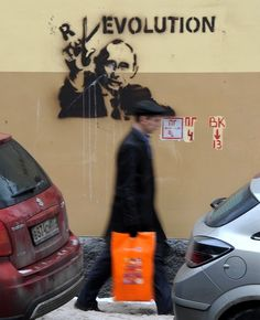 A man walks by graffiti of Russian Prime Minister and presidential candidate Vladimir Putin in Moscow. Photo by Andrey Smirnov /AFP /Getty Images.