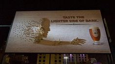 Billboard with shadow art made by different heights of beer bottle caps. Watch the video!