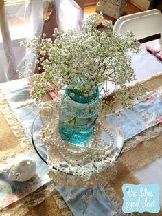 Un centro de mesa vintage y muy económico con mason jars y baby's breath.