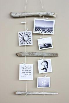 wandgestaltung aus hölzernen stöcken undn hängenden fotos