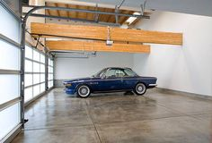 Open garage concept with less is more. We like the touch of rustic with the wood beams. Looking to remodel your garage? Porte Cochere, Stained Concrete, Concrete Floors, Lofts, Garage Pictures, Building A Garage, Cool Garages, Ultimate Garage, Hotel Door