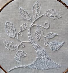 The base of the tree is made with Long and short stitch; and the center of this, Satin stitch overlaid with Herringbone stitch. From the top to bottom as viewed here are Colonial knots, 4 rows of S…