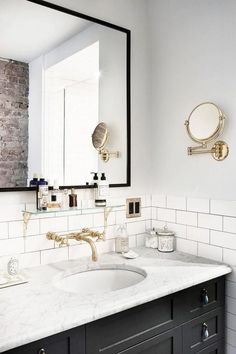 Bathroom goals. Black vanity, marble counter, white subway tile, wall mounted faucet, brass accordion wall mirror