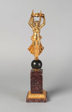 A French gilt bronze model of Nike, late 19th /early 20th century, the winged figure holding aloft the wreath of Victory standing on a green patinated ball, , on a gilt bronze mounted red marble base - Dim: 39cm high