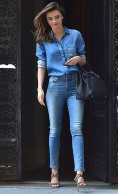 Miranda Kerr con camisa vaquera; pitillos de cintura alta; shopping bag negro y sandalias con estampado de leopardo.