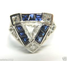 ANTIQUE ART DECO TRIANGLE DIAMOND ENGAGEMENT RING  CIRCA ~ 1930'S 1 TRIANGULAR BRILLIANT CUT NATURAL DIAMOND~ .50 CARAT  COLOR ~ E - F CLARITY ~ VS 1 - VS 2  MEASUREMENT OF CENTER DIAMOND ~ 6.60 MM x 5.85 MM x 1.96 MM 3 FRENCH CUT NATURAL DIAMONDS ~ .30 CARAT  COLOR ~ F - G CLARITY ~ VS 1 DIAMOND TOTAL WEIGHT ~ .80 CARAT 9 STEP CUT TAPERED BAGUETTE SYNTHETIC SAPPHIRES ~ .54 CARAT T.W.  FINGER SIZE ~ 7