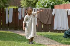 Little African-American girl playing in front of drying laundry. Raleigh Tavern Alley Colonial Williamsburg. Photo by David M. Doody.