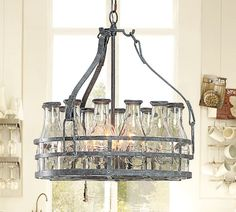 """MILK BOTTLE CHANDELIER. A dozen clear class milk bottles- Each embossed with a cow and the words """"fresh milk,"""" an authentic dairy-farm look."""