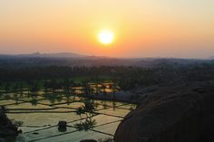 View from the top of a boulder strewn cliff, looking over the rice fields and mountains in the distance of Hampi, during sunset. Hampi, Cliff, Bouldering, Fields, Distance, Blessed, Rice, India, Celestial