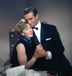 """Still of Lois Maxwell and Sean Connery in Dr. No (1962). This is the very first costume Bond wore when audiences saw him for the first time in the casino scene when he uttered """"Bond, James Bond."""" It's the famous midnight blue shawl collar dinner jacket with turn-back cuffs, made by Anthony Sinclair."""