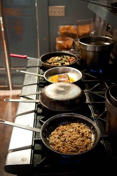 Pans sautéing on the stove at West First Pizza