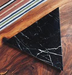 Equilateral Triangle ( each side is 12). Overal measurements: approx. 12 x 10.25 x .75  This handmade black marble triangle board with natural white veining is ideal as a sculptural trivet, for displaying or serving (think cheese, sushi, charcuterie), or a fabulous place to leave your jewelry. We have added round leather legs to make it easier for you to pick it up.  Wipe clean with a damp cloth, not microwave or dishwasher friendly.  This board is made from natural stone and **patterns will…