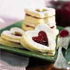 Raspberry Heart Cookies - Cute cookie sandwiches are made with a raspberry filling and attractive heart cut-out in the center.