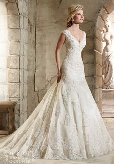 "Wedding Dresses and Wedding Gowns by Morilee featuring Alencon Lace Appliques on Net with Crystal Beading and Scalloped Hemline Over Soft Satin This Alencon lace bridal gown features a scalloped hemline, and stunning illusion back with covered button detail. Delicate crystal beading adds the perfect touch of sparkle. Available in Three Lengths: 55"", 58"", 61"" . Colors Available: White, Ivory, Ivory/Coco"