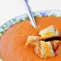 Roasted tomato soup with grilled cheese croutons: 6 cups (3 pints) cherry tomatoes  3 tablespoons olive oil  1 teaspoon salt  1/2 teaspoon pepper  2 tablespoons unsalted butter  2 garlic cloves, minced  1 cup chopped onion  1 (28-ounce) can diced tomatoes  4 cups chicken broth  1/2 teaspoon thyme  1 cup whipping cream
