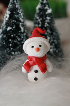 This listing is for one hand sculpted polymer clay snowman. He stands approximately 2 tall and can be customized - you choose the color of his scarf and hat! He can also be used as a Christmas ornament, so please choose whether you would like an eyehook or not. If you need a larger size or color that is not listed, please convo me and I can make a special listing for you. *******************  Each figurine is made entirely by me from start to finish. They are sculpted individually so no two…