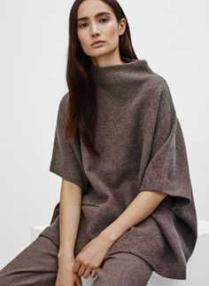 I like the interesting structure of this cape.  The clean/unique neckline and the subtle pockets.  Is purposely oversized to be a cape but doesn't feel like you're swimming in it.
