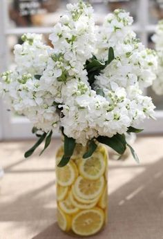 Instead of basic clear vases, fill one with lemon or lime slices. from Hostess Hacks- Entertaining Hacks - House Beautiful Vintage Centerpieces, Rustic Wedding Centerpieces, Wedding Table Decorations, Wedding Table Settings, Centerpiece Ideas, Spring Decorations, Rustic Vases, Rustic Table, Lemon Centerpieces