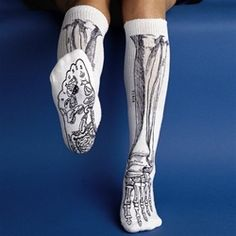 "Go skinless with this amusing design and learn the real names for your big toe, shin bone and more. Knee length.    the bones in your lower leg and foot shown on knee length socks  "" soles show reflex points  "" black print on white socks or white print on black socks  "" adult sized  "" 70% acrylic $15"