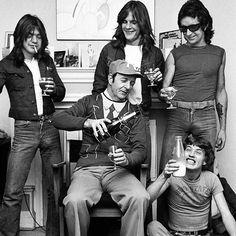 UNITED KINGDOM - JANUARY 01: Photo of AC/DC; L-R (back): Malcolm Young, Mark Evans, Bon Scott; (front): manager Michael Browning , Angus Young (drinking milk), drinking champagne at press reception in WEA offices (Photo by Dick Barnatt/Redferns)