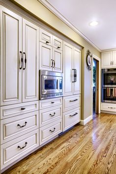 Awesome kitchen wall with refrigerator (far end), microwave, and lots of storage. Pretty cabinets pop against the refinished oak floors.