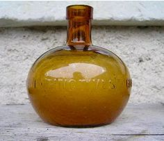 """Rare amber glass fire grenade, with smooth body and pontilled base. The embossing around the central band reads """" GRENADES  EXTINCTIVES  GRENADES  DU  PROGRES  """" ,"""