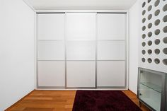 Living room sliding wardrobe doors. 3 door 3 panel equal split with white glass panels and anodised silver aluminium frame.