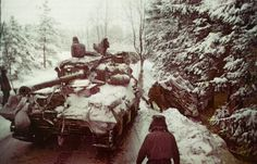 Tanks along an icy road in the Ardennes Forest during the Battle of the Bulge.