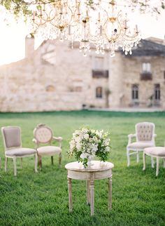 chandelier hanging from tree and vintage furniture at luxe wedding | photo: Jose Villa
