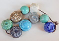 Set Beads matt . The set consists of = 9 beads of porcelain and stoneware ,hand carved ,have cream , green , blue and grey glazes , the smaller bead measures 13 x 13 mm. and the largest 18 x 18 mm. By Mª Carmen Rodriguez Martinez ( Majoyoal ) https://www.facebook.com/groups/CeramicArtBeadMarket/
