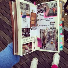scrapbook layouts, journal with photos, a drawing and writing, cutouts, tickets, held by an arm, shoes in the background
