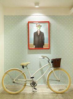 Decoração que incorpora a bicicleta e candy color, como essa entrada com papel de parede e quadro.