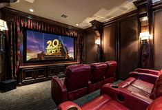Movie theater room-curtains around the TV screen adds to the feel of the room as well as the wall sconces.