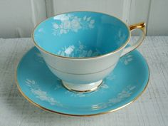 Vintage Aynsley tea cup & saucer, turquoise blue, tipped in gold gilt with faint white roses.