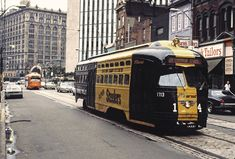 Talk about #PIttsburgh spirit! Pictured here is PCC #1713, dressed up in Steelers colors, rolling down Liberty Avenue. The large building in the background to the left is Penn Station, still used by Amtrak today.