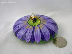 Hand painted flower rock.  A rock painted into a purple daisy with water droplets on the petals. A cute little bumble bee has landed on it.  The rock measures about 31/8 (8cm) long and 2 3/8 (6cm) wide and 1.25(5.80cm) high The bee is glued on with stong glue. Its sealed with an exterior varnish and can be outside.  Thank you for visiting!  Please check out my other flowery rocks; https://www.etsy.com/ca/shop/NightOwlFineArt?ref=l2-shopheader-name&s...