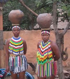 Africa | Zulu woman carrying traditional pots.  Photographer ?