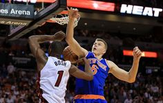 Kristaps Porzingis of the New York Knicks goes up against Chris Bosh of the Miami Heat during a game at American Airlines Arena