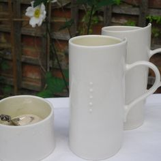 A handbuilt porcelain mug perfect for latte. Glazed inside a pale green or celadon blue, clear on the outside. Simply decorated with tiny porcelain dots.  14cm high x 6.5cm  Dishwasher and microwave safe.