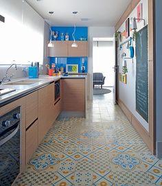 Com cores escolhidas pela moradora Renata Leoni, a cozinha é um local sem frescuras. O ladrilho hidráulico foi instalado aleatoriamente e há um quadro pintado com tinta lousa, em que crianças e adultos se divertem