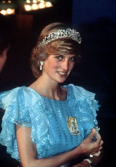 Princess Diana at a dinner hosted by The Province Of New Brunswick. The Princess is wearing the diamond Spencer Tiara. She has accessorized her pale blue evening dress with a broad silver belt and silver clutch bag. Diana's outfit is by fashion designer Bruce Oldfield.