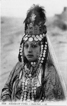 Africa   Young Ouled Nail girl, with facial tattoos wearing a coin headdress which drapes around her neck and chest, a metal crown with feathers, a veil falling behind her shoulders and a taffeta gown. Algeria   ©Lévy Fils et Cie   ca. 1905   Scanned old postcard image.