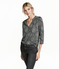 Black/patterned. Wide-cut top in soft, airy jersey. V-neck and buttons at front, 3/4-length puff sleeves, seam at yoke, and rounded hem with short slits at