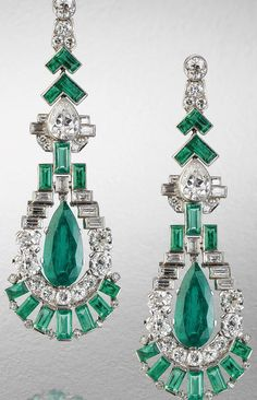 A fine pair of art deco emerald and diamond pendent earrings, circa 1920.   Each articulated geometric surmount set with baguette-cut emeralds, brilliant, pear and baguette-cut diamonds, suspending a pear-shaped emerald swing drop, within a stepped surround of similarly cut diamonds and emeralds, diamonds approximately 4.60 carats total.