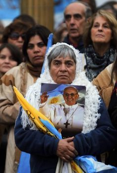 Woman holds image of Pope Francis as people in Buenos Aires gather in main square to watch broadcast of his inaugural Mass   A woman holds an image of Pope Francis as people watch the televised broadcast of the pope's inaugural Mass in Plaza de Mayo in Buenos Aires, Argentina, March 19. (CNS photo/Marcos Brindicci, Reuters)
